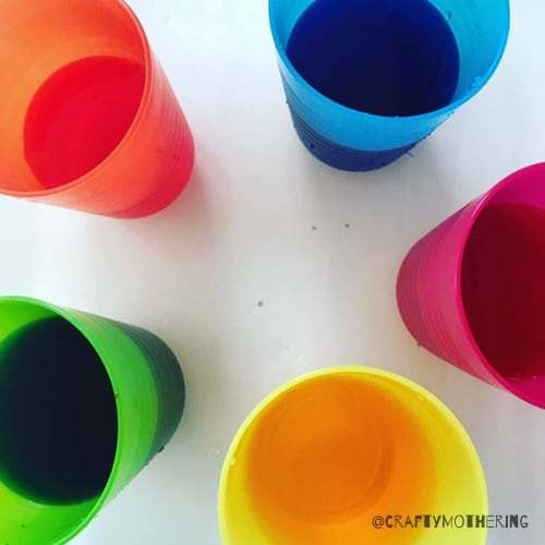 cups of colourful water dyeing easter eggs